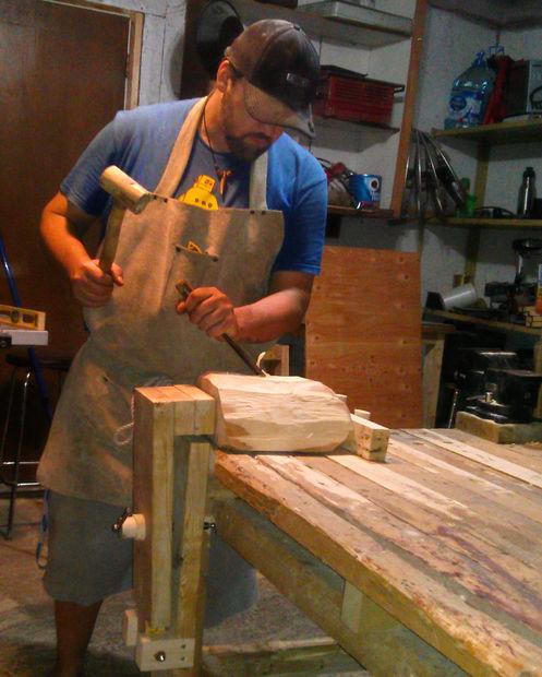 плотник с киянкой возле стола