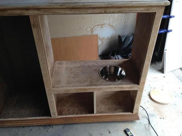 В шкафу вырезано отверстие и вставлена миска