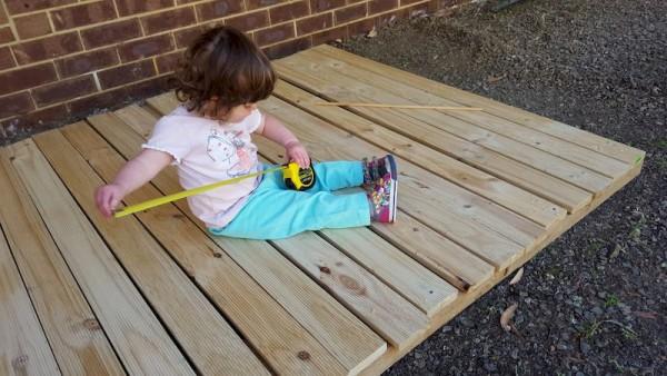 Маленькая девочка сидит на деревянном настиле