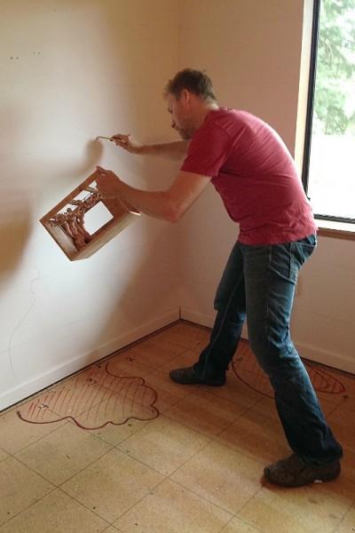 Мужчина наносит разметку на стену