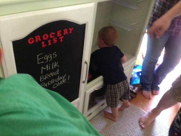 Ребёнок играется с детской кухней