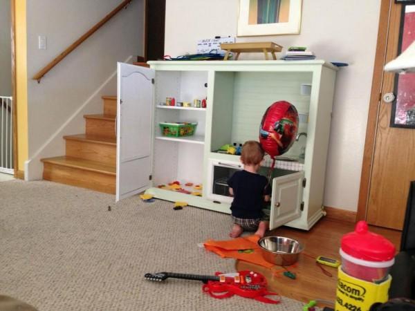 Ребёнок играет с детской кухней