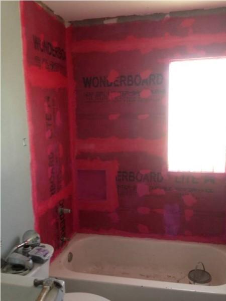 Стены ванной комнаты покрыты красной грунтовкой