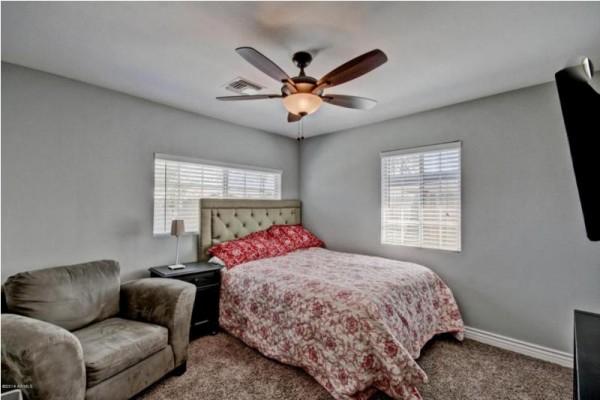 Спальня с кроватью, креслом и вентилятором на потолке