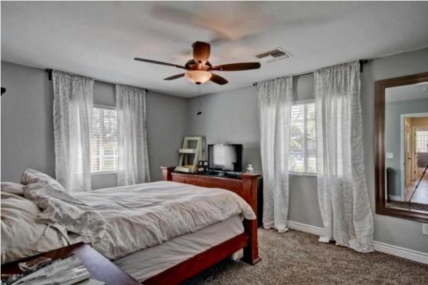 Спальная комната кроватью, комодом, телевизором и вентилятором на потолке