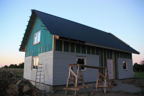 Дом наполовину облицован, на перереднем плане деревянные леса