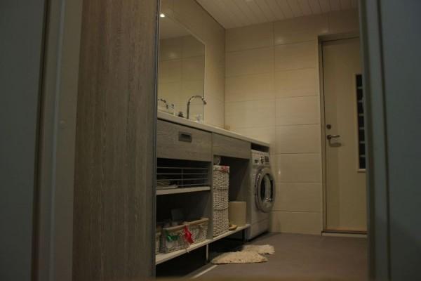 В ванной комнате стелажи и стиральная машинка, вид сбоку