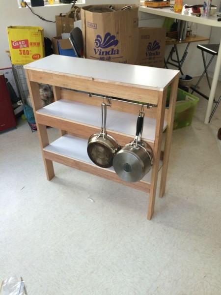 На крючках кухонного шкафа висит посуда