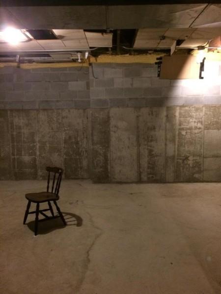 В подвальном помещении стул по центру комнаты