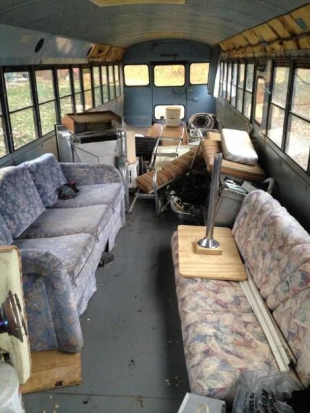 В салоне старого автобуса поломанные диваны и мусор