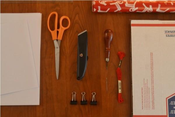 Бумага, ножницы, резак, шило, игла, красные нитки, зажимы и картон