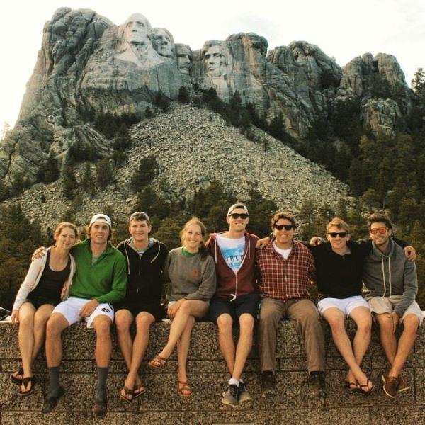 Молодые люди сидят у подножия горы