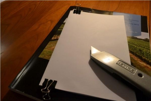Тетрадь зафикстрована зажимами и канцелярский нож
