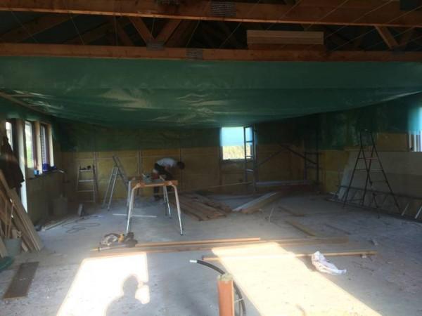 Человек зашивает потолок и стены комнаты полиэтиленом
