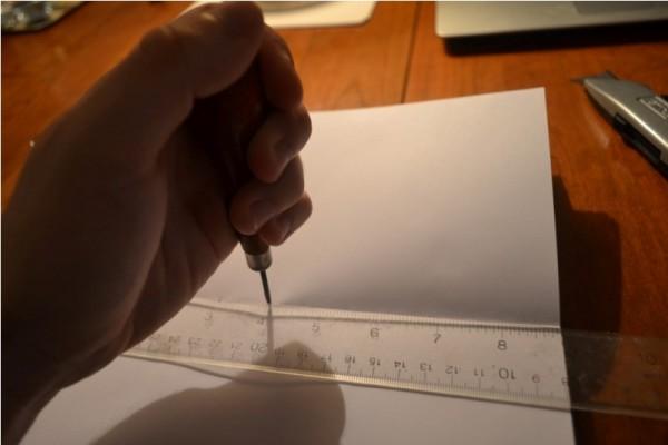 Человек пробивает шилом отверстия в бумаге