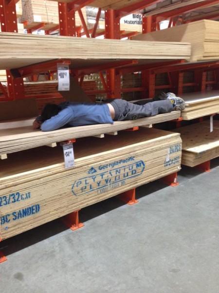 Человек лежит в магазине на полке с фанерой