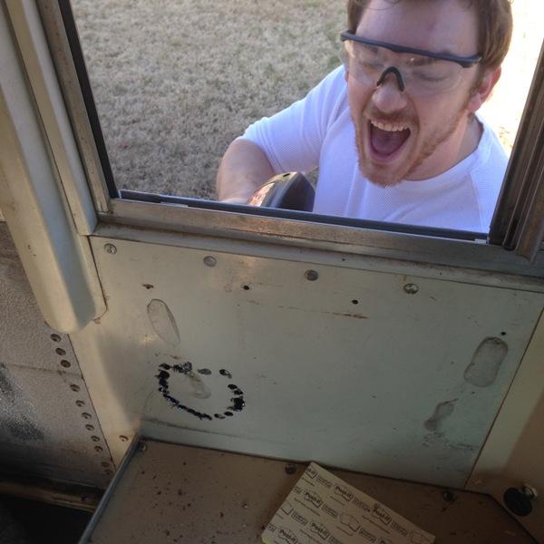 Человек сверлит отверстие дрелью в корпусе автобуса