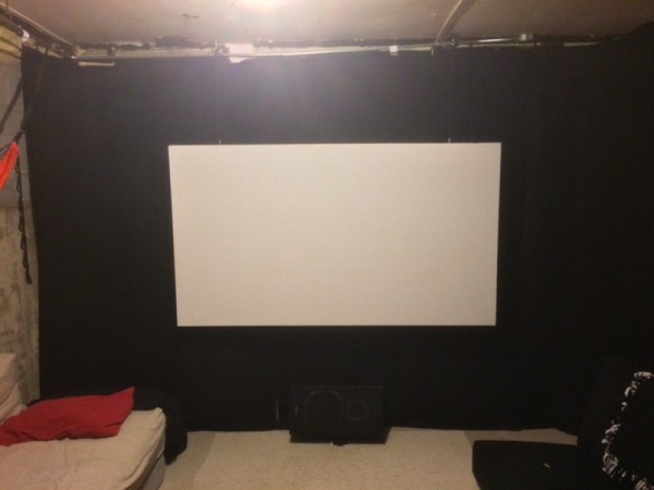 Экран на фоне чёрной стены