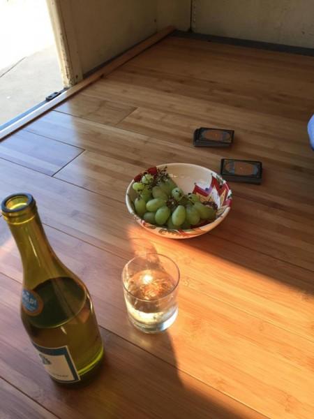На полу бутылка шампанского и виноград