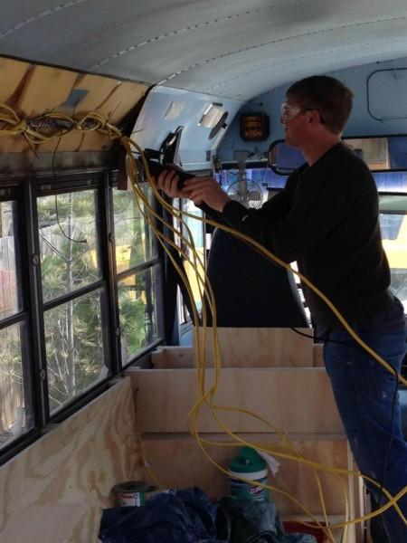 Человек прокладывает электропроводку по салону автобуса