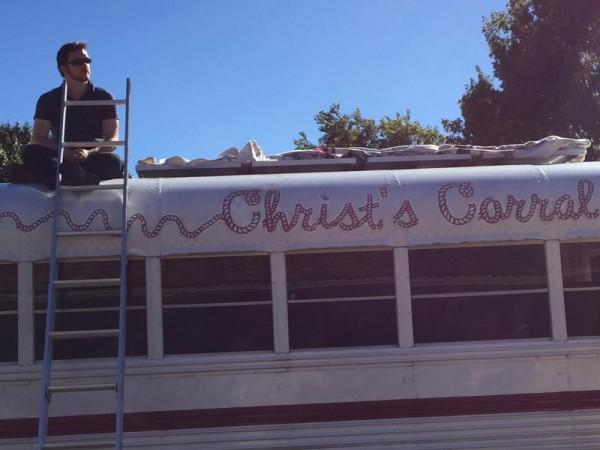 Человек сидит на крыше автобуса