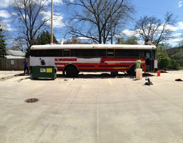 Люди шпаклюют поверхность автобуса