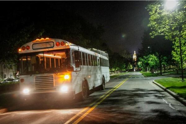 Автобус на ночной дороге с включёнными фарами