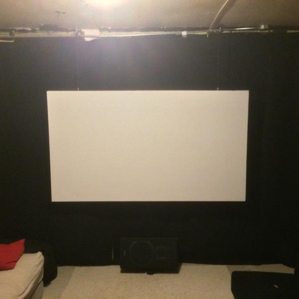 Белый экран на фоне чёрной стены