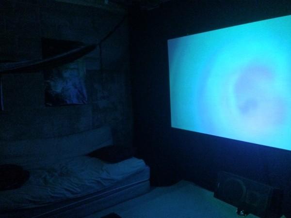 LED фонарь светит на экран в тёмной комнате