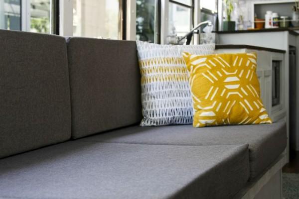 На диване белая и жёлтая подушка