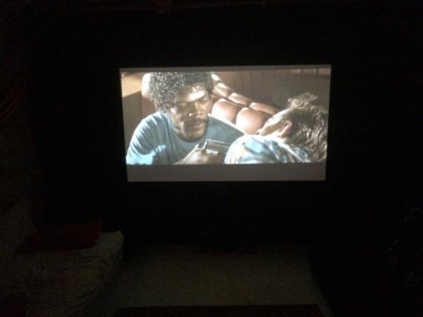 От экрана освещается комната