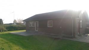 Вид на дом с травяным газоном и уложенной плиткой