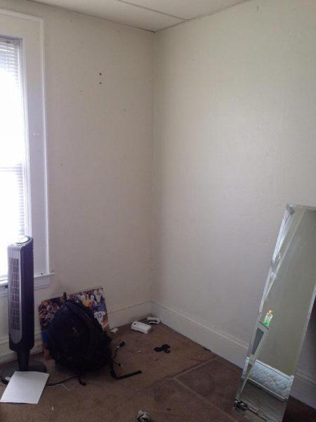 В углу комнаты мусор, зеркало и обогреватель