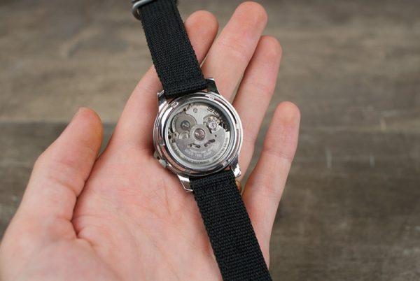 Механические часы в руке, вид сзади