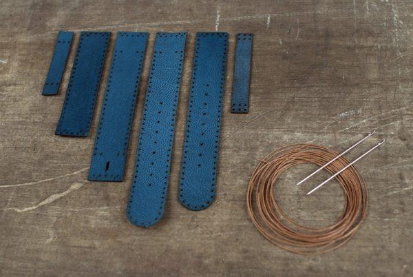 Куски кожаного ремешка и нитки с иголками