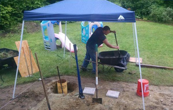 Человек лопатой в тачке перемешивает бетон