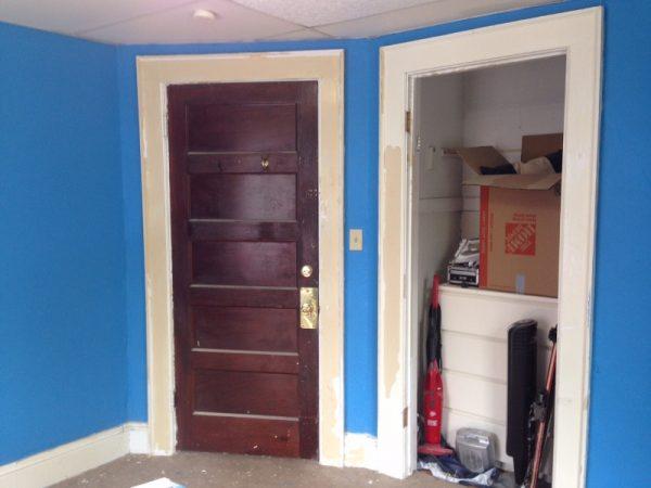 Окрашенные стены комнаты в синий цвет, вид на входную дверь