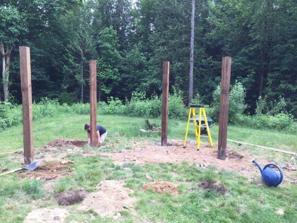 Человек закапывает деревянный столб