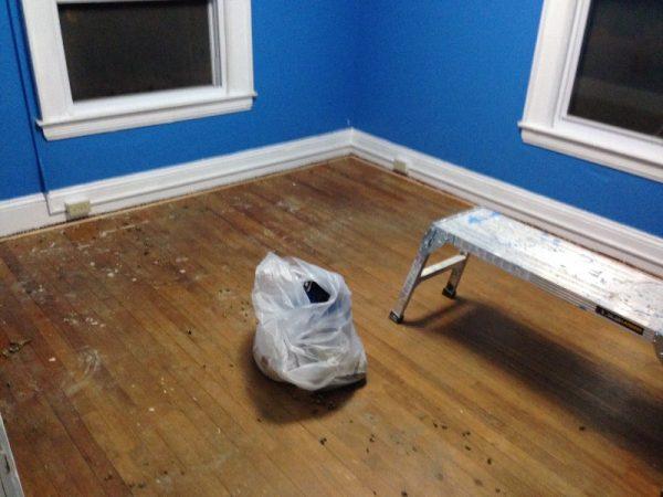 Деревянный пол в комнате и пакет с мусором