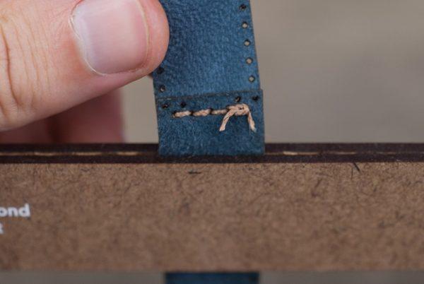 В конце шва на коже завязан узел