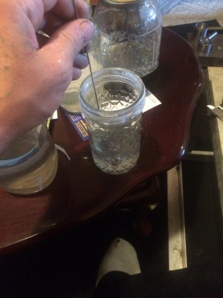 Монета в стеклянном стакане с раствором