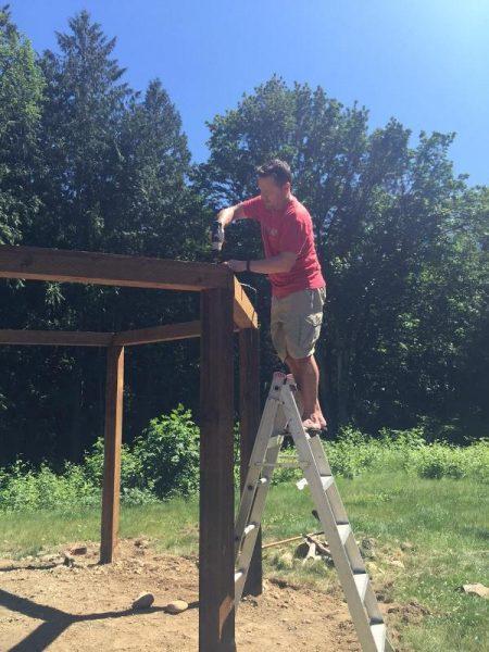 Мужчина на лестнице прикручивает деревянные балки
