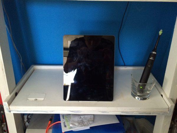 На полке шкафа зеркало и электрическая зубная щётка в стакане