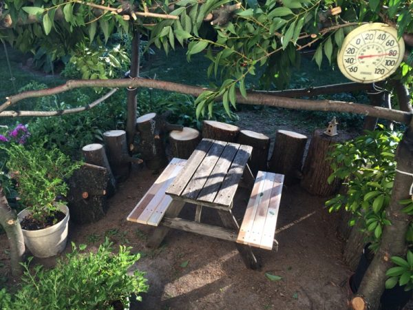В шалаше деревянный стол и лавки