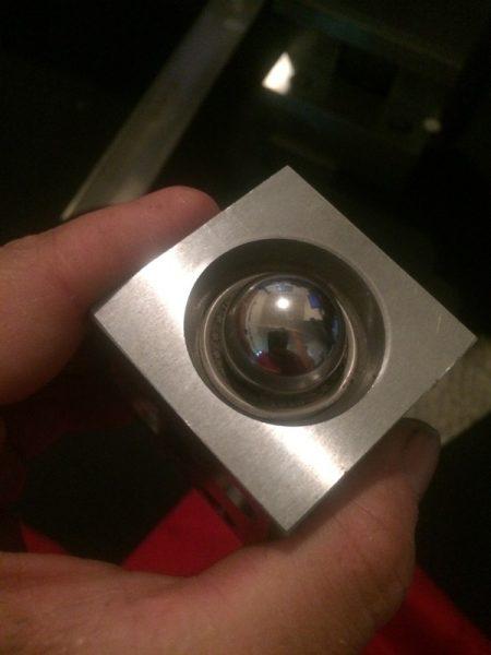 Оправка с изогнутой монетой и металлический шарик