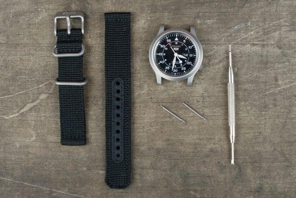 Чёрный ремешок от часов, часы и пинцет