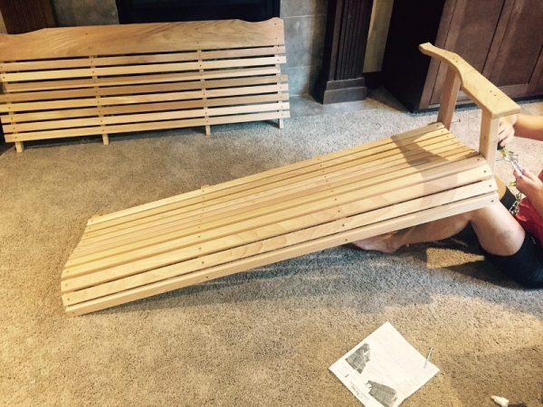 Мужчина собирает деревянное сиденье для качели