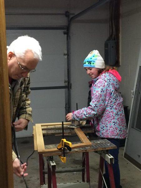 Девочка и мужчина шлифуют поверхность шкафа