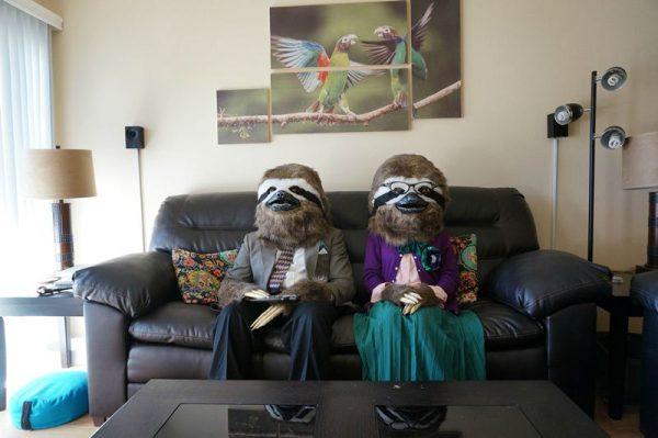 Люди сидят на диване в масках и костюмах