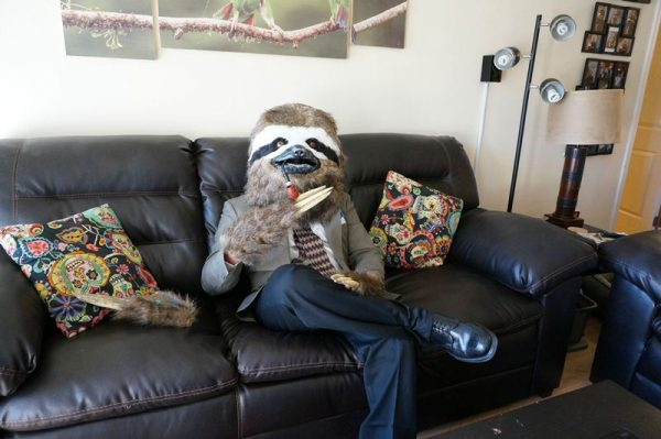 Человек в маске Арчибальда сидит на коженном диване